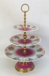 Fruteira com 3 platôs, em porcelana, decorada com diversas cenas de galanteio em policromia. Detalhes em dourado. Estrutura em bronze dourado e trabalhado. Alt. 37,5cm e Diam. prato maior 25,5cm.