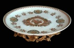 Magnífico e grande centro de mesa em medalhão de porcelana oriental com florais e belos efeitos craquelados e pés ricamente trabalhados com guirlandas e volutas em material sintético. Medida 36 cm de diâmetro.