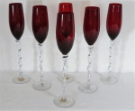 Seis long fluts em vidro moldado ao gosto de Murano na cor rubi, haste translúcida torcida, base circular. Med. 35 cm alt x 6 cm diâmetro.