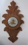 Relógio de parede em madeira ricamente entalhada, mostrador de metal, algarismos romanos, movimento a quartz, sem funcionamento aparente - Peça da década de 70. Med. 85 x 47 x 10 cm.