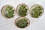 MAISON BLANCHE- Quatro pratos decorativos em cerâmica vitrificada, galeria central decorado com cacho de coco e folhagens, bordas com detalhes. Marcados na base. Med. 20 cm diâmetro.