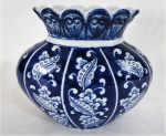Vaso oval em porcelana, fundo azul cobalto decorado com desenhos florais em alto relevo em tom branco. Med. 19 x 22 x 11 cm.