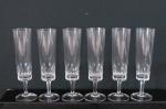 Conjunto de seis fluts em fino cristal  translúcido , base redonda, haste facetada, bojo lapidação dita dedão. Med. 18 cm alt.