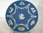 WEDGWOOD ENGLAND -Medalhão em porcelana biscuit inglês no tom azul, com marca da manufatura Wedgwood na base. . Decorados com figuras de querubins  em relevo. Marcado a crivo na base. Inglaterra, meados do séc. XX. Med. 23 cm diâmetro.