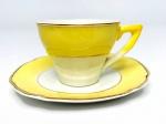 BARROS LOUREIRO & FILHOS, ADELINAS SÃO CAETANO - Elegante xícara para café em porcelana, formato sextavado e borda em movimento decorada em policromia com vivo amarelo e contornos em vibrante ouro. Acompanha seu respectivo pires. Possui registro da manufatura na base.