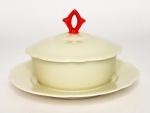 KAHLA ALEMANHA - Graciosa manteigueira em porcelana creme, com borda em movimento. Acompanha a sua respectiva tampa com pega em vivo laranja. Possui registro da manufatura na base. Mede14 cm de diâmetro x 8,5 cm de altura.