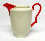KAHLA ALEMANHA - Graciosa leiteira em porcelana creme, com borda em movimento, alça e bico em vivo laranja. Possui registro da manufatura na base. Mede 10 cm de altura.