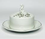 STEATITA - Elegante mantegueira em porcelana, ornamentada com delicadas flores pintadas à mão em tons de cinza e branco, borda em movimento e contorno em filete prata. Acompanha a sua respectiva tampa com pega. Possui registro da manufatura na base. Mede 16 cm de diâmetro.