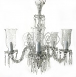 EUROPA - Magnífico lustre em cristal europeu translucido para cinco velas, ricamente adornados com penduricalhos de cristais e braços curvos. Acompanha as suas respectivas mangas com bordas em movimento, decoradas  com lapidação em motivo floral. mede 70 x 60 cm.