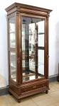 MOBILIÁRIO - Vitrine estilo império, em madeira nobre (vinhático) com porta e laterais em vidro, prateleiras internas e fundo espelhado. Gaveta inferior com entrada de chaves em bronze. Med. 223x107x64 cm.