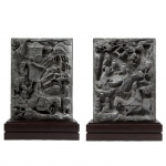 Raríssimo par de placas executas em pedra representando cenas do cotidiano, figuras orientais, cavalos e liteira. China, Dinastia Ming (1368-1644). 49 x 36 cm (sem base). 60 x 40 cm (com base).
