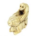 Netsuke em marfim, representando coelho e macaco. Japão, Meiji, Séc. XIX. Assinado. 4 x 4 cm. Apresenta documentação de registro em cartório com firma reconhecida pelo proprietário, datando a época da peça e indicando procedência.