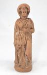 """TANAGRA, Grécia. Antiga escultura em grega em Terracota retratando Deusa com adorno na cabeça. Desgastes do tempo e restauro no pescoço. Peça para pesquisa. Datação à confirmar.  Med. 25 cm. AS ESCULTURAS DE TANAGRA eram figuras de terracota produzidas a partir do século IV AC, e que em homenagem à cidade de Tanagra , onde muitas dessas peças foram escavados, receberam o nome da região. No entanto, eles foram produzidos em muitas cidades. Eles eram revestidos com uma pasta branca líquida e às vezes eram pintadas em tons naturalistas com aquarelas, como a famosa """"Dame en Bleu"""" (""""Lady in Blue"""") no Louvre. Eles foram amplamente exportados para todo o mundo grego antigo. Essas figuras foram feitas em muitos outros locais do Mediterrâneo, incluindo Alexandria , Tarentum na Magna Grécia , Centuripena Sicília e Myrina na Mísia.Embora não sejam retratos, as figuras de Tanagra representam mulheres reais - e alguns homens e meninos - em trajes do dia a dia, com acessórios familiares como chapéus, grinaldas ou leques. Algumas peças de personagens 1 podem ter representado figuras tradicionais da Nova Comédia de Menandro e outros escritores. Outros continuaram uma tradição anterior de figuras de terracota moldadas usadas como imagens de culto ou objetos votivos . Normalmente, eles têm cerca de 10 a 20 centímetros de altura.Algumas estatuetas de Tanagra tinham um propósito religioso, mas a maioria parece ter sido inteiramente decorativa, muito parecido com seus equivalentes modernos do século 18 em diante. Dados os costumes funerários gregos, eram colocados como bens mortuários nos túmulos de seus proprietários, 2 muito provavelmente sem qualquer sentido de que serviriam ao falecido na vida após a morte, da maneira que é comum na arte funerária do antigo Egito ou China. Não parecem ter sido feitos especialmente para sepultamento.Os coraplastros , ou escultores dos modelos que forneciam os moldes, se deleitavam em revelar o corpo sob as dobras de uma himação lançada sobre os ombro"""
