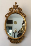 Elegante e grande espelho em madeira talhada , formato oval, decorado  com arranjos florais e encimada por ânfora. Revestido com folhas de Ouro. Exemplar antigo. Dimensões: 1 metro x 50 cm.