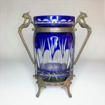 Belíssimo vaso em Cristal Double azul, ricamente lapidado, com guarnição em  metal dourado. Alças no formato de ser mitológico e pés no formato de conchas. Dimensões: 21 cm x 19 cm x 10 cm.