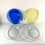 Conjunto com 4 pratos, translúcidos e nas cores azul e amarelo. Marcas de uso. Dimensões: 23 cm diâmetro.