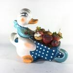 Escultura em gesso de pato com cestas de frutas. Exemplar com pequeno desgastes. Dimensões: 21 cm x 26 cm x 14 cm.