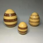 Conjunto com 3 grandes ovos em cerâmica esmaltada na cor marfim, decoradas com faixas horizontais  em tons de marrom. Pequeno bicado  no exemplar da direita. Dimensões: 20 cm x 14 cm (maior peça).