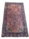 Tapete persa floral com tons tijolo, roxo e azul. Em bom estado. Apresenta pontos de desgaste. Medida: 205x116 cm.