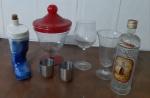 Lote com sete itens, uma garrafa vazia formato de bota, um pote com tampa, duas taças, duas cálices em metal e uma garrafa vazia.