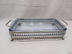 Travessa retangular em vidro temperado, com suporte em metal prateado avarandado com 2 alças e pés. Medindo a travessa 34,5cm x 20cm x 5cm de altura.