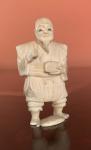 NETSUKE EM MARFIM, representando personagem COM CAIXA . Perda de quatro dedos do pé direito - JAPÃO. MEDIDAS; 5 X 2,5.